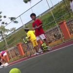 Tennis coach Hafizi teaching kids serve
