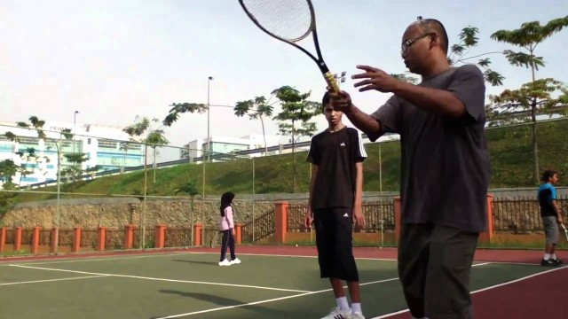Tennis Coach Edie giving tennis tips for beginner player at Cyberjaya